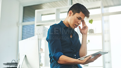 Buy stock photo Shot of a young businessman using a digital tablet and looking unsure in a modern office