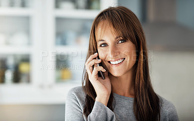 Buy stock photo Cropped shot of a middle aged woman talking on her cellphone at home