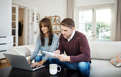 Buy stock photo Shot of a couple using a laptop while looking at paperwork