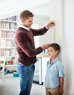 Buy stock photo Shot of a man measuring his son's height against the wall