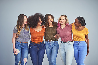 Buy stock photo Studio shot of a group of attractive young women embracing against a gray background