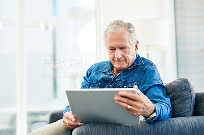 Buy stock photo Shot of senior man using a digital tablet on the sofa at home