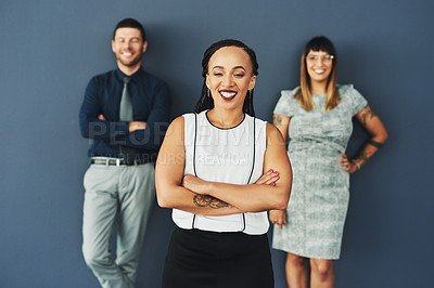 Buy stock photo Portrait of a group of confident young businesspeople standing with their arms folded against a grey background