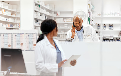 Buy stock photo Cropped shot of a handsome young male chemist talking to a colleague while making a phonecall in the pharmacy with a colleague in the background