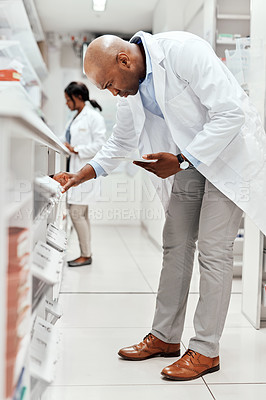 Buy stock photo Full length shot of a handsome young male chemist working behind a counter in the pharmacy with a colleague in the background