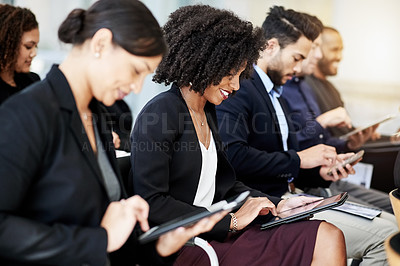 Buy stock photo Shot of a group of businesspeople using their digital tablets during a conference