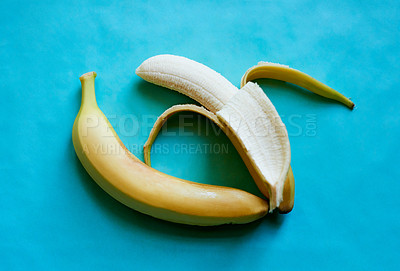 Buy stock photo Studio shot of two bananas lying in a suggestive position against a blue background