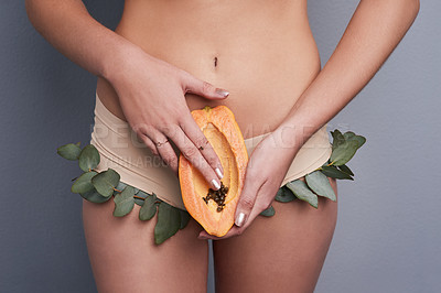 Buy stock photo Cropped studio shot of a woman wearing leafy underwear and holding a papaya against a grey background