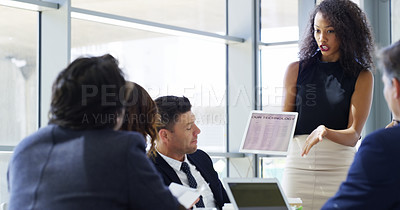 Buy stock photo Cropped shot of a businesswoman using a digital tablet while giving a presentation to her colleagues in an office
