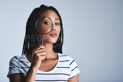 Buy stock photo Studio shot of a beautiful young woman posing with a magnifying glass