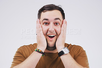 Buy stock photo Studio portrait of a handsome young man looking surprised against a grey background