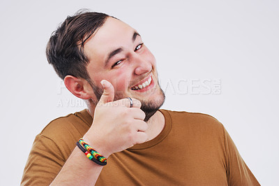 Buy stock photo Studio portrait of a handsome young man giving a thumbs up against a grey background