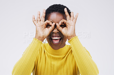 Buy stock photo Studio shot of a young woman making a funny face against a gray background