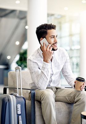 Buy stock photo Shot of a focused young businessman calling on his phone and drinking coffee while waiting for his flight at the airport