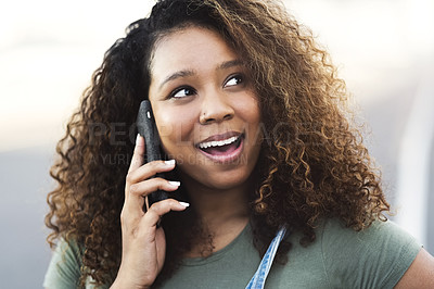Buy stock photo Shot of an attractive young woman answering a call while walking through the city