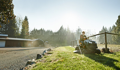 Buy stock photo Shot of a mature woman driving a lawnmower on a farm
