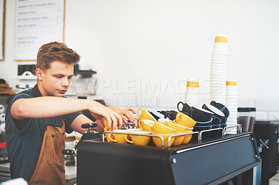 Buy stock photo Shot of a young man preparing coffee in a cafe