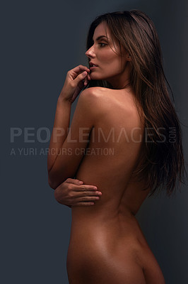 Buy stock photo Studio shot of a beautiful young woman posing nude a dark background