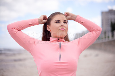 Buy stock photo Cropped shot of an attractive and sporty young woman standing on the beach during her workout