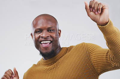 Buy stock photo Studio shot of a handsome young man looking cheerful and dancing against a grey background