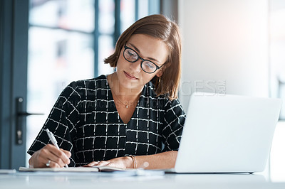 Buy stock photo Cropped shot of a focused young businesswoman writing on a notebook in an office