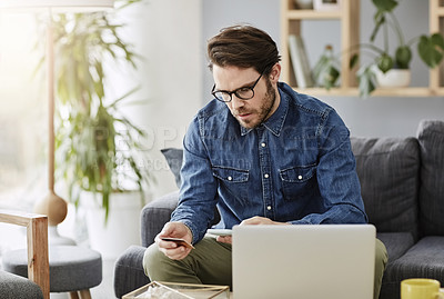 Buy stock photo Shot of a young man shopping online while sitting on his couch at home