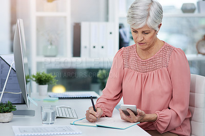 Buy stock photo Shot of a mature woman writing down details from her cellphone to her diary in her office at work