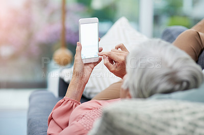Buy stock photo Rearview shot of a mature woman using her cellphone while relaxing on a sofa at home