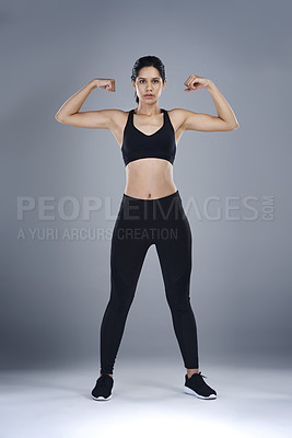 Buy stock photo Full length shot of a sporty young woman flexing her biceps against a grey background
