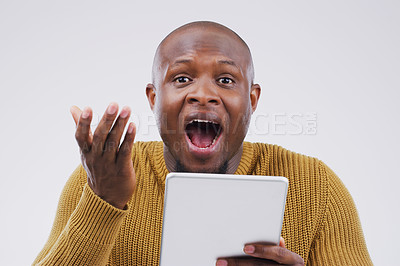 Buy stock photo Studio shot of a young man looking surprised while using a digital tablet