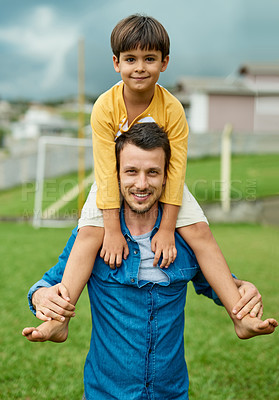 Buy stock photo Portrait of a cheerful father carrying his young son on his shoulders outdoors