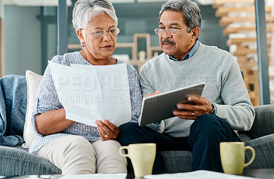 Buy stock photo Shot of a mature couple using a digital tablet while going through paperwork together at home