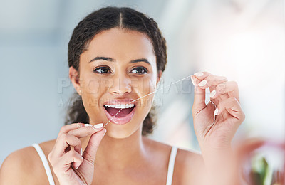 Buy stock photo Cropped shot of an attractive young woman flossing her teeth in the bathroom at home