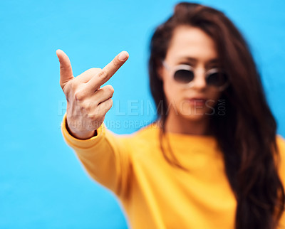 Buy stock photo Shot of a attractive young woman showing middle finger while  posing against a blue background
