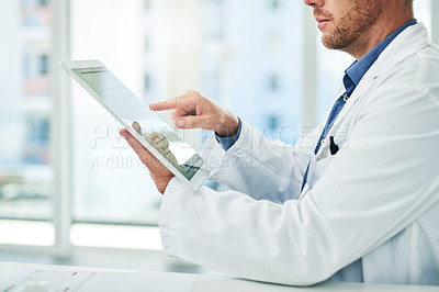 Buy stock photo Cropped shot of a unrecognizable doctor browsing on a digital tablet inside of his office during the day