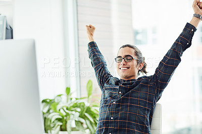 Buy stock photo Shot of a young designer cheering while working in an office
