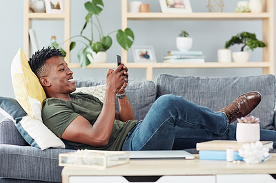 Buy stock photo Shot of a young man using a cellphone while relaxing at home