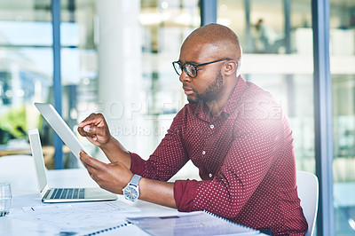 Buy stock photo Cropped shot of a young designer using a digital tablet at his desk