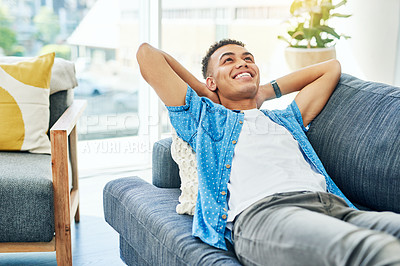 Buy stock photo Shot of a cheerful young man  seated on a sofa while relaxing at home during the day