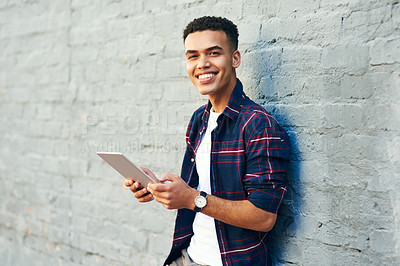 Buy stock photo Portrait of a cheerful young man leaning against a wall while browsing on a digital laptop during the day