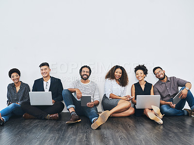 Buy stock photo Studio portrait of a group of businesspeople using digital devices against a white background