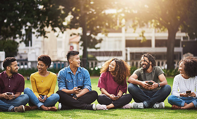 Buy stock photo Shot of a group of friends using their cellphones while sitting together