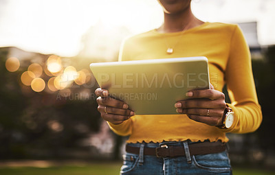 Buy stock photo Cropped shot of an unrecognizable woman using a digital tablet outdoors