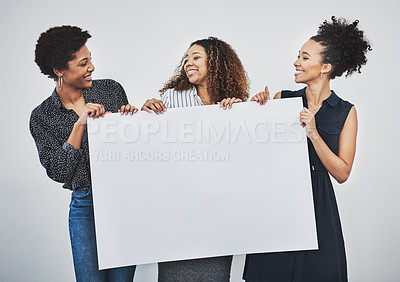 Buy stock photo Studio shot of a group of young businesswomen holding a blank sign against a gray background