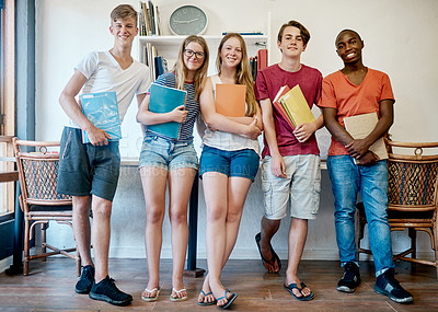 Buy stock photo Portrait of a group of cheerful young students standing in the classroom while holding their school books inside during the day