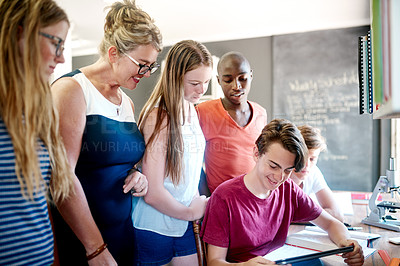 Buy stock photo Cropped shot of a group of cheerful young students looking on a laptop together while the teacher joins them