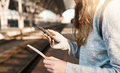 Buy stock photo Cropped shot of an unrecognizable young woman sending text messages while waiting for a train