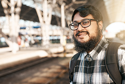Buy stock photo Cropped portrait of a handsome young man waiting at a train station