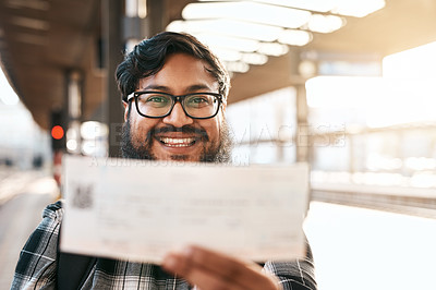 Buy stock photo Cropped portrait of a handsome young man showing you his boarding pass while waiting for a train