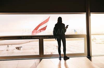 Buy stock photo Rearview shot of a young woman looking out the window at an airport